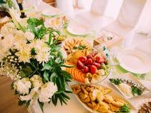 果子的上述看法和在婚礼安置的不同的盘在ther巨大的白色花束附近制表 免版税库存图片