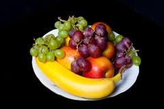 果子的不同的类型在一块白色陶瓷板材的在黑ba 免版税库存照片