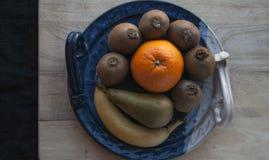 果子的构成在一个装饰蓝色盛肉盘的在有一块黑布料的一个木板在背景中 免版税库存图片