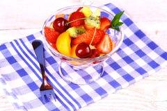从果子的沙拉在玻璃碗和点心分叉 库存图片
