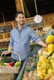 果子的英俊的年轻人购物在超级市场 免版税库存图片