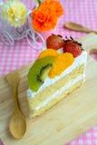 果子蛋糕片断与猕猴桃、草莓和桔子的 免版税库存图片