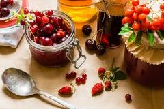 果子蜜饯和未加工的草莓、樱桃、花揪和红浆果莓果在厨房用桌上 库存图片