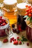 果子蜜饯和未加工的草莓、樱桃、花揪和红浆果莓果在厨房用桌上 免版税库存照片
