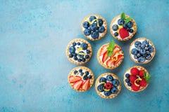 果子馅饼或蛋糕用乳脂干酪和莓果在绿松石桌上从上面 可口五颜六色的酥皮点心点心 免版税库存照片
