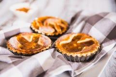 果子馅饼洒与糖粉用在白色木背景的桃子果酱与洗碗布 免版税库存图片
