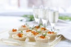 果子馅饼用乳脂干酪和红色鱼子酱关闭 快餐用红色鱼子酱用开胃酒 轻的背景 图库摄影