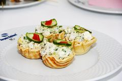 果子馅饼用沙拉和绿色黄瓜在白色板材 库存照片