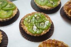 果子馅饼用焦糖和坚果 与猕猴桃的可口开胃馅饼在白色背景 库存图片