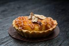 果子馅饼用焦糖和坚果 在黑暗的木背景的可口开胃馅饼 免版税图库摄影