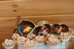 果子馅饼用莓和奶油、蛋糕和甜在假日背景 可口点心和棒棒糖承办酒席概念 免版税库存照片