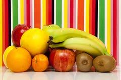 果子 苹果计算机,梨,桔子,葡萄柚,普通话,猕猴桃,香蕉 多色背景 免版税库存图片