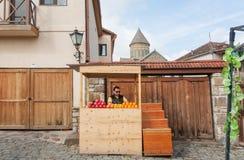 结果实贸易商在卖苹果,桔子,在狭窄的街道上的石榴的柜台 图库摄影