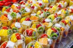 水果沙拉在市场上的塑料杯子安排了 免版税图库摄影