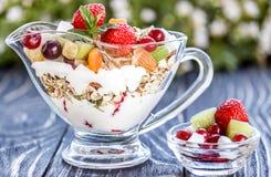 水果沙拉特写镜头用莓果、酸奶和格兰诺拉麦片在玻璃弓 免版税库存图片