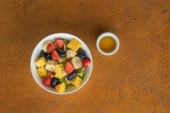 水果沙拉用在白色碗的蜂蜜在石背景 免版税库存照片