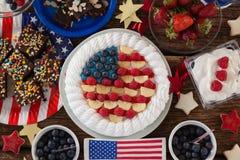 水果蛋糕和各种各样的甜食物在木桌上安排了 库存图片
