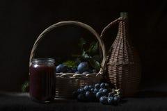 果酱、李子、葡萄和篮子 库存照片