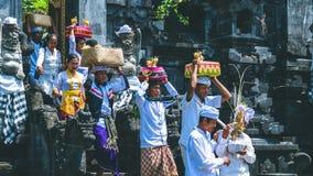 果阿LAWAH,巴厘岛,印度尼西亚- 2016年11月3日:传统衣裳的巴厘语人运载在仪式以后保佑礼物在 免版税库存照片