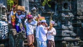 果阿LAWAH,巴厘岛,印度尼西亚- 2016年11月3日:传统衣裳的巴厘语人运载在仪式以后保佑礼物在 图库摄影