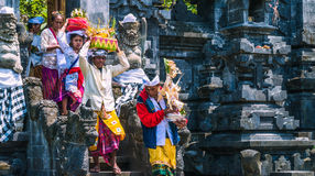 果阿LAWAH,巴厘岛,印度尼西亚- 2016年11月3日:传统衣裳的巴厘语人运载在仪式以后保佑礼物在 免版税库存图片