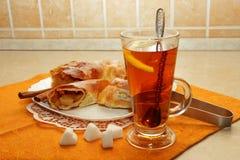 果馅奶酪卷家被烹调,裁减入片断和一个杯子热的茶 免版税库存图片