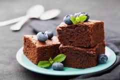 果仁巧克力堆装饰了蓝莓和薄荷叶 在绿松石板材的巧克力蛋糕在葡萄酒黑色桌上 自创酥皮点心为 库存照片