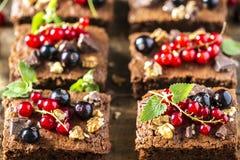 果仁巧克力巧克力蛋糕用新鲜的莓果、无核小葡萄干和薄菏 免版税图库摄影