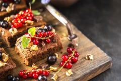 果仁巧克力巧克力蛋糕用新鲜的莓果、无核小葡萄干和薄菏 库存照片