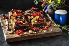 果仁巧克力巧克力蛋糕用新鲜的莓果、无核小葡萄干和薄菏 图库摄影