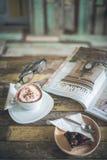 果仁巧克力蛋糕、热的咖啡和杂志 免版税库存照片