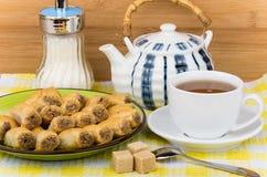 果仁蜜酥饼离子板材、糖罐和茶在桌布 库存照片