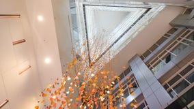 枝形吊灯由在现代大厦,底视图的五彩纸屑制成 金黄水晶,抽象背景 闪耀的背景 免版税库存图片