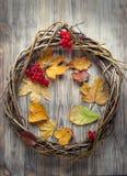 枝杈花圈在一个老木门的用秋天莓果和a 免版税库存图片