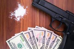 枪、药物和金钱在木背景 顶视图 免版税库存图片