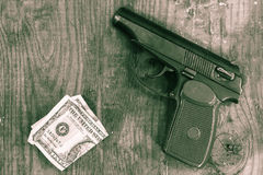 枪和金钱在木桌上 免版税库存图片
