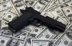黑枪手枪和金钱美元背景 库存图片