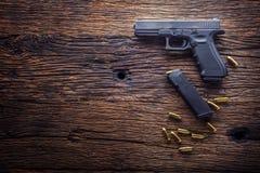 枪手枪 9 mm在土气橡木桌上和子弹撒布的手枪枪 免版税库存图片