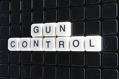 枪枝管制文本词标题说明标签盖子背景背景 字母表信件在黑反射性背景的玩具块 免版税库存照片