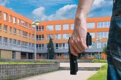 枪枝管制概念 年轻人武装人拿着手枪手中在公开近的学校 免版税库存照片
