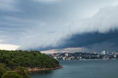 架子滚动在悉尼港口的云彩前面 库存照片