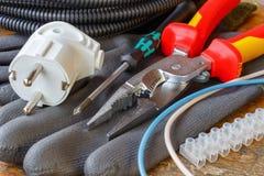 架线的组合钳子与一个螺丝刀、电子插座和电线接头运作的手套的在木桌上在车间 免版税库存照片