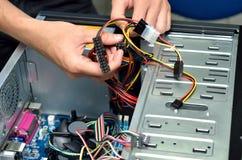 架线计算机mainboard的技术员的手 免版税库存图片