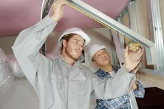 架设墙壁绝缘材料盘区的工作员在建造场所 免版税库存图片