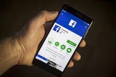 柏林,德国- 2017年11月19日:现代智能手机在手中有Facebook的 免版税库存照片