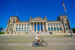 柏林,德国- 2015年6月06日:在柏林的中心,与他的bycicle的一个未认出的人十字架的历史建筑 库存图片