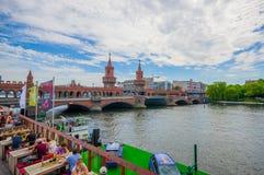 柏林,德国- 2015年6月06日:狂欢在oberbaumbrucke,在边的人havind松弛时间下的河十字架 免版税库存图片