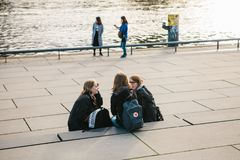 柏林, 2017年10月3日:一个小组学生的女孩朋友坐在附近位于的江边 免版税库存图片