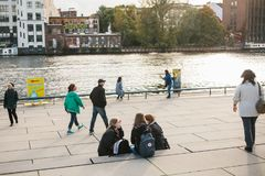 柏林, 2017年10月3日:一个小组学生的女孩朋友坐在附近位于的江边 免版税库存照片