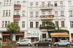 柏林, 2017年10月1日:有装饰的阳台、商店和咖啡馆的美丽的地道房子与人和汽车 免版税库存照片